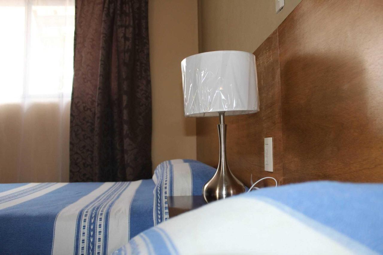Lámpara, buró, cortinas habitación tipo Booking Planta Alta