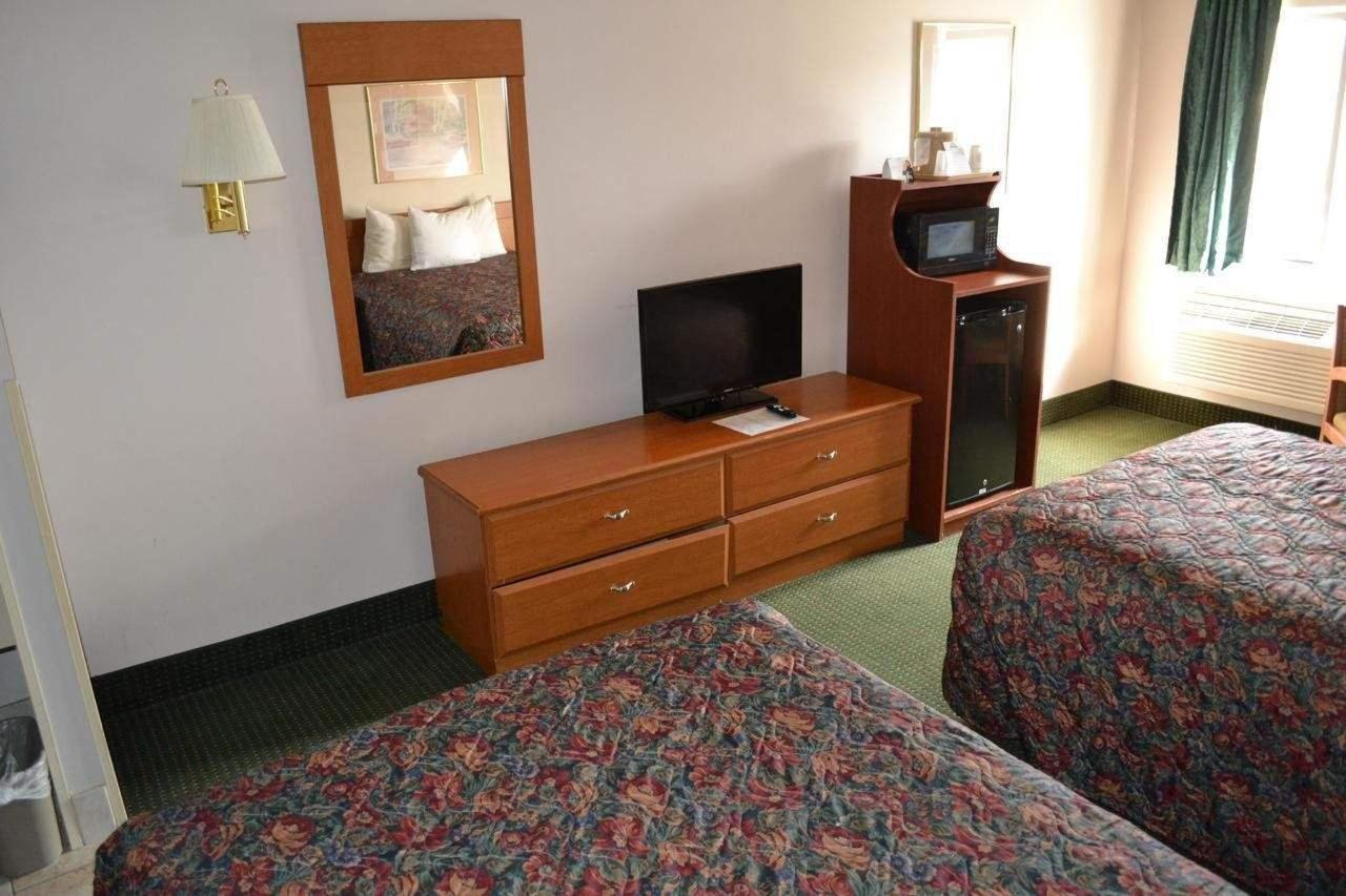 two bed room showing refrigerator, microwave and flat screen tv.jpg