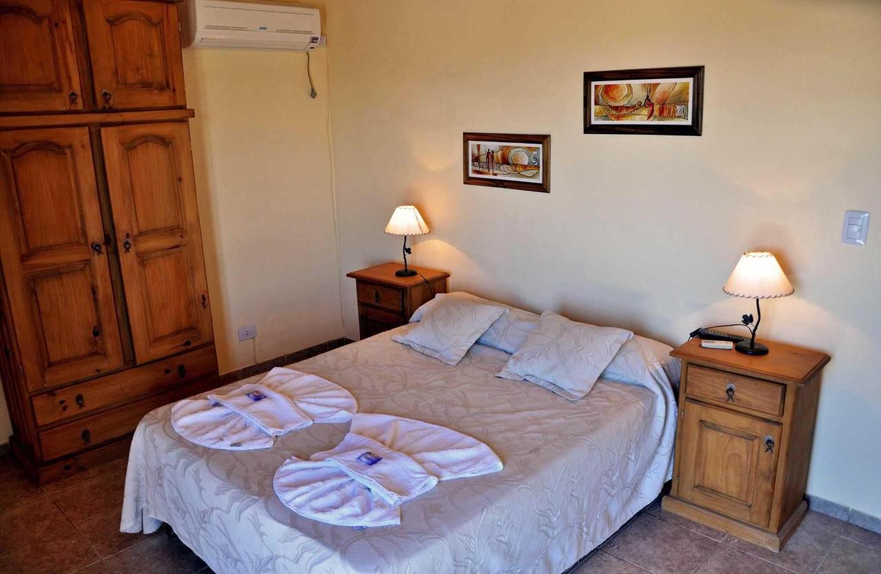 Dormitorio cabaña II con somier, aire acondicionado y balcón con vista al lago y las sierras